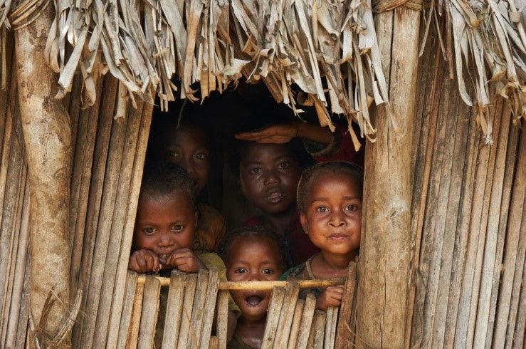 Enfants à la fenêtre d'une hutte à Madagascar.